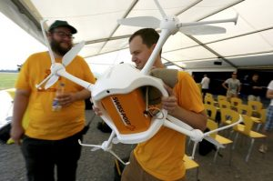Swiss Post and Swiss WorldCargo drone is carried by members of the 'Matternet' team during a presentation at Bellechasse airfield in Bas-Vully near Fribourg, Switzerland, July 7, 2015. REUTERS/Pierre Albouy
